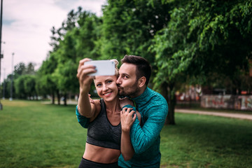 Sport, technology and healthy lifestyle concept. Couple making selfie after workout.