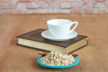 Oats flakes in dish on wood table