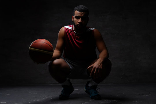 African-American basketball player in sportswear squatting with a ball on a dark background.