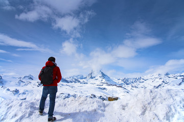 Man in red jacket is looking Matterhorn peak on Gornagrat peak, Zermatt, Switzerland