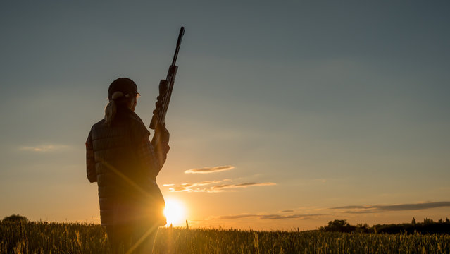Silhouette of woman hunter. It stands in a picturesque place with a gun at sunset. Sports shooting and hunting concept