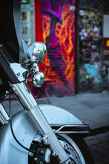 The front wheel of a motorcycle and a headlamp with graffiti wall background