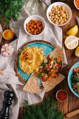 Top view of plate with hummus served with different kinds on vegetables and pita