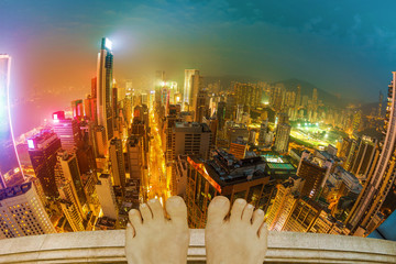 Depressed and stressed Hong Kong woman on roof of a skyscraper thinking of suicide, over Tokyo cityscape at night. with city lights of Wan Chai district. Fisheye wide view.