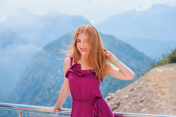 Beautiful red hair woman resting on a mountain near the sea. In summer, sunny day. Concept of vacation. Young lady enjoying the fresh air and nature, looking at the mountains and sea