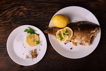 Baked fish with lemon, spices and herbs on white plate on wooden background without head