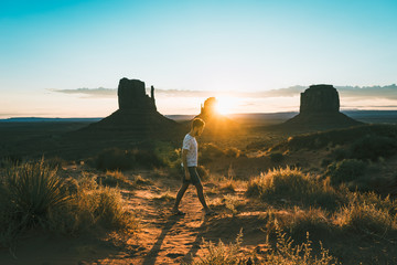 young man near rock formation in monument valley, USA