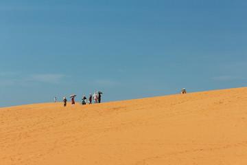 Group of   tourists with umbrellas in desert landscape / red sand dune in  Mui Ne, Vietnam