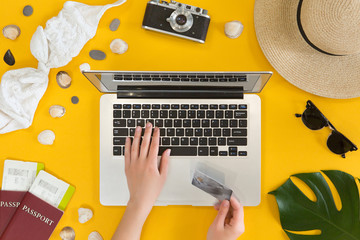 Booking and payment travel online concept, top view, flat lay. Woman hand holding credit card near laptop, overhead view of desktop with traveler accessories