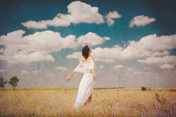 photo of beautiful young woman standing in the field on the wonderful sky background
