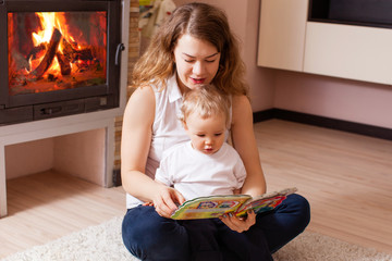 mother is reading for her son near fireplace