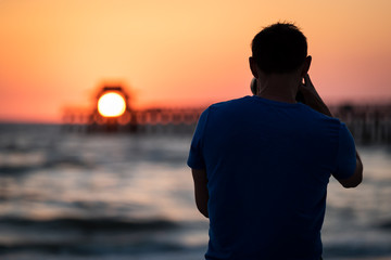 Naples, Florida pink, red and orange sunset in gulf of Mexico with sun setting inside Pier bokeh, back of young man photographer videographer taking pictures filming landscape