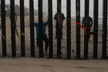People taking part in morning workout are seen on the Mexico side of the border wall from the U.S. near San Diego, California