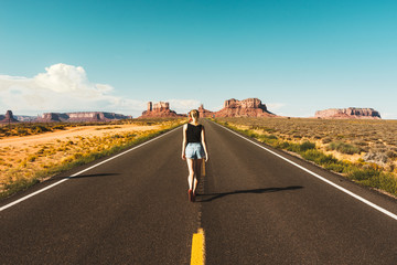 Young woman on the road over monument valley, USA Wall mural