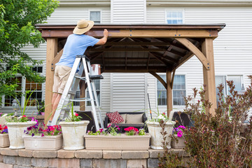 Man staining a backyard gazebo behind his house