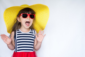 Joyful surprised little girl in colorful clothes and sunglasses standing on white background. Kid's fashion. Summer holidays.