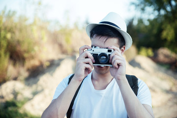 Hipster man taking photos in nature with retro camera