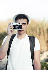 Young man taking photos with retro camera in nature