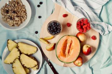 Flat-lay of tasty summer raw healthy vegetarian vegan detox clean eating breakfast with fresh summer seasonal fruits and berries served.