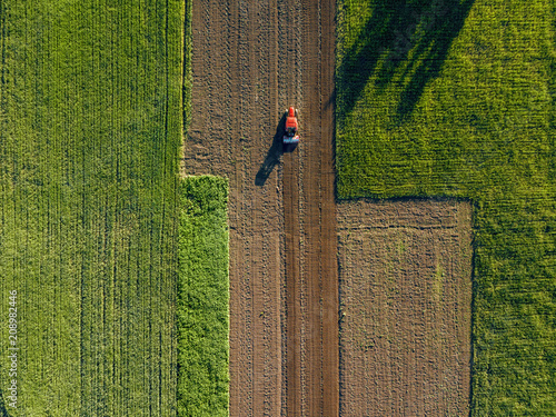 Wall mural Aerial view from the drone, a bird's eye view of agricultural fields with a road through and a tractor on it in the spring evening at sunset in the summer