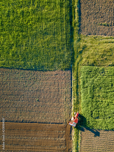 Wall mural Aerial view from the drone, a bird's eye view of agricultural fields with a road through and a tractor on it in the spring evening at sunset
