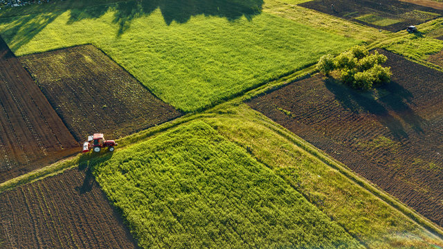 Aerial view from the drone, a bird's eye view of agricultural fields with a road through and a tractor on it in the spring evening at sunset