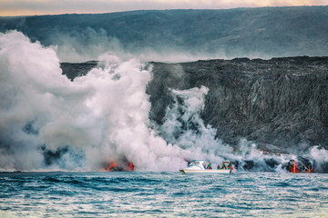 Hawaii volcano eruption boat tour. Tourists on ocean cruise travel activity watching the lava reaching the water with toxic fumes. Dangerous excursion on Big Island.