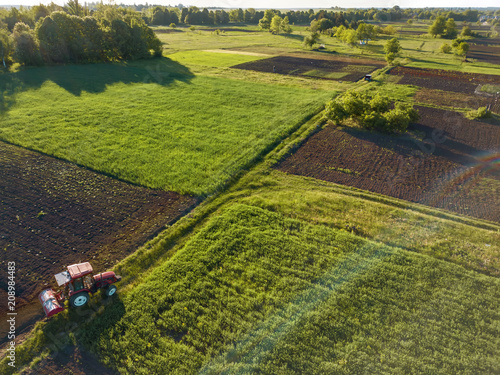 Wall mural Aerial view from the drone, a bird's eye view of agricultural fields with a road through and a tractor and car on it in the spring evening at sunset