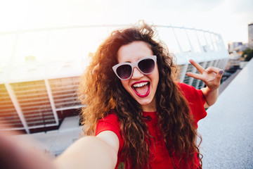 Attractive smiling girl with curly hair showing a peace sign while taking a selfie, looking at camera, wearing sunglasses.