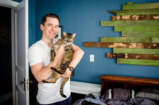 Young man holding cat