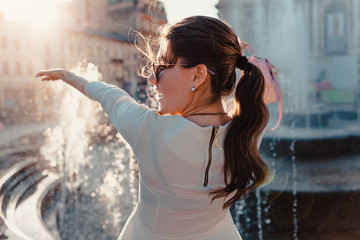 Happy young woman tourist enjoys fountain. Summer travel. Vacation and holidays concept