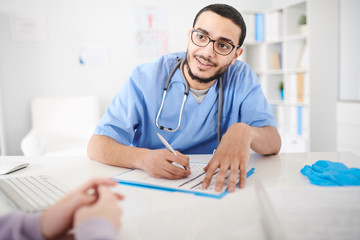 Portrait of young Middle-Eastern doctor wearing glasses sitting at desk in office and listening intently to unrecognizable patient while making notes on clipboard
