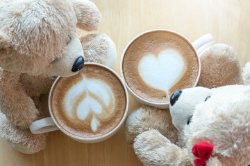 Top viwe of two teddy bears and coffee cup on pine wooden table.