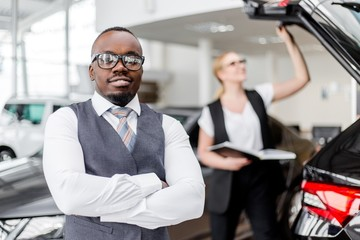 African man with glasses is in the foreground against the background of the girl checking the trunk of the car