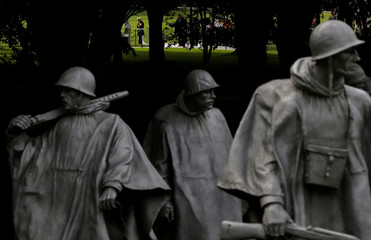A member of the U.S. military is seen through the trees walking with the Korean War Veterans Memorial in the foreground in Washington