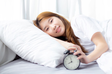 Beautiful of portrait asian young woman turn off alarm clock in morning, wake up for sleep with alarm clock, relax and lifestyle concept.
