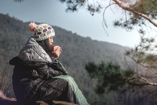 Beautiful girl relaxing on the hill sitting in a sleeping bag and drinking hot drink, enjoying holidays, travel concept.