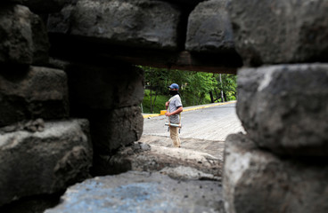 A demonstrator stands behind a barricade at the Universidad Nacional Autonoma de Nicaragua (UNAN) during a protest against Nicaragua's President Daniel Ortega's government in Managua