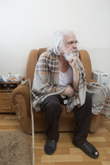 Old sick lonely man in the armchair at home