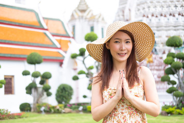 Young Asian woman with smile greeting in thai style, travelling Bangkok at Wat arun temple