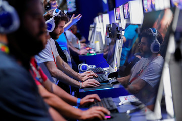 Attendees play video games at E3, the world's largest video game industry convention in Los Angeles
