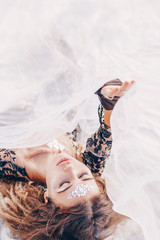 beautiful young fashionable woman lying on sand at sunset
