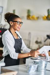 friendly african american shop assistant using pos terminal to input orders at restaurant