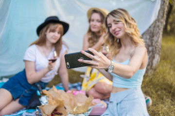 Group of girls friends making picnic outdoor. They make selfie photo from smartphone. bachelorette, party