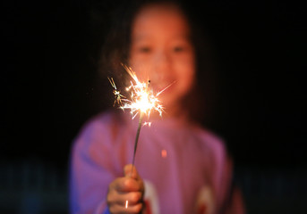 Little Asian child girl enjoy playing firecrackers. Focus at fire sparklers. Fotomurales