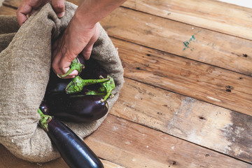Hand takes eggplant from bag on wooden boards