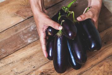 Hands take few eggplants on wooden boards