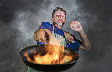 shocked messy man with apron holding pan in fire burning the food in kitchen disaster and unskilled and unexperienced terrible home cook