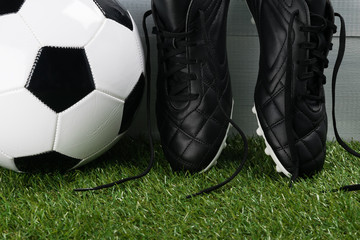 ball and leather shoes for soccer player close-up on green grass