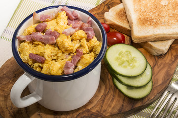 scrambled eggs with roasted bacon in an enamel mug